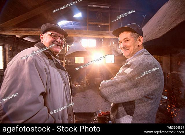 portrait of two confident senior blacksmith standing with crossed arms in the traditional workshop