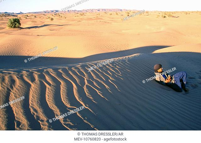 Morocco - a Moroccon Arab rests at a stretch of sand dunes near the palmery of Oulad Driss