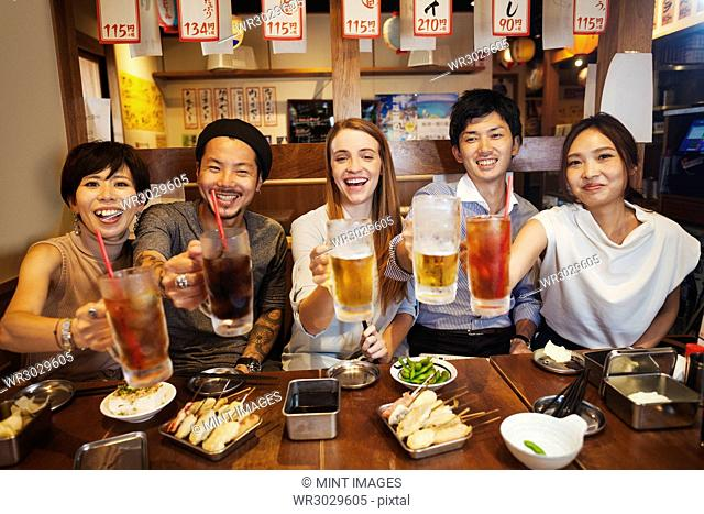 Five people sitting sidy by side at a table in a restaurant, holding large glasses with soft drinks and beer