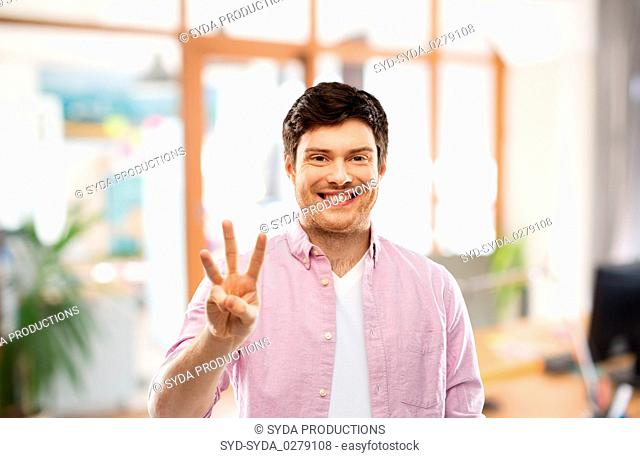 young man showing three fingers over office room