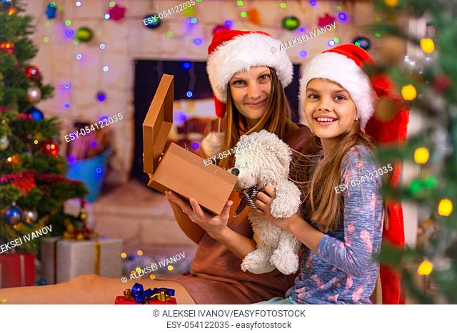 Mom and daughter opened the Christmas box with a gift and looked into the frame