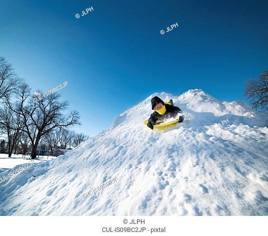 Boy sledding on snow