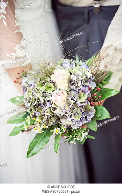 Close-up of bride and groom holding bridal bouquet