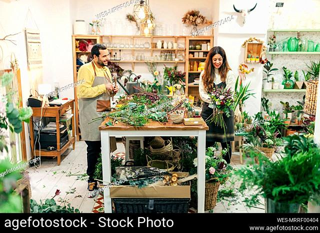 Man and woman working while standing at flower shop