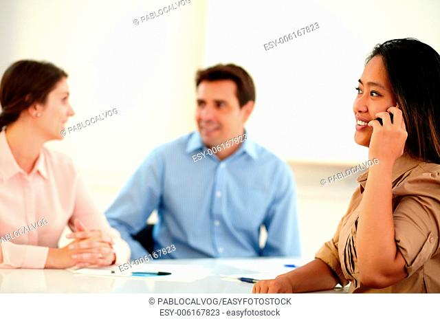 Portrait of a charming asiatic woman conversing on her cellphone during a meeting on office