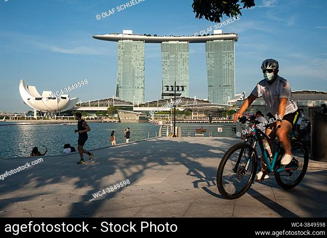 Singapore, Republic of Singapore, Asia - A man wearing a protective face mask cycles on his bike along the waterfront by the Singapore River during the lasting...