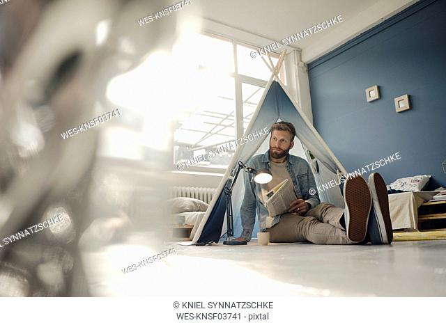 Man camping in his living room, reading the newspaper