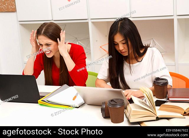 Happy students sitting in library and studying. Two girls preparing for lessons, classes or exams. Ladies using laptop computers