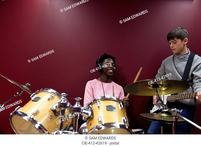 Teenage musicians recording music, playing drums and guitar in sound booth