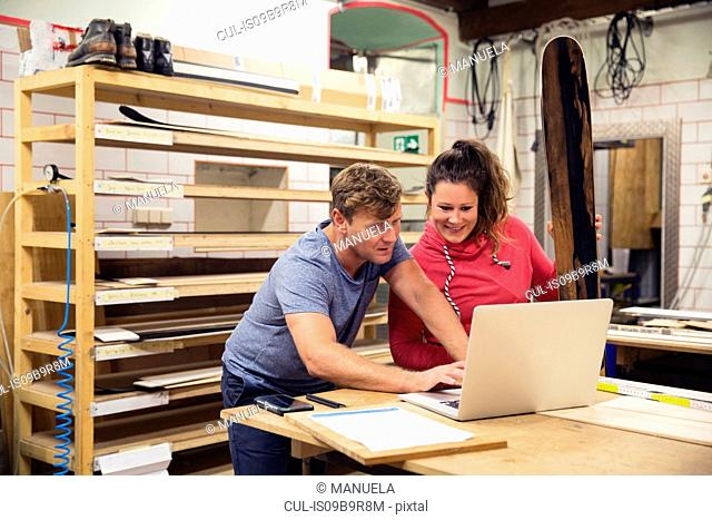 Man and woman in workshop, using laptop