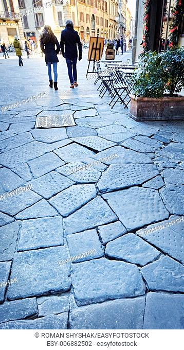 Florence old paving and tourists on background