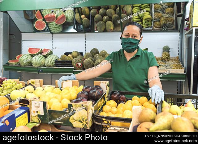 a shopkeeper with a mask poses in front of her fruit shop