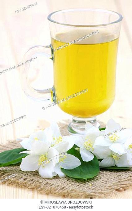 glass of jasmine tea and jasmine flowers