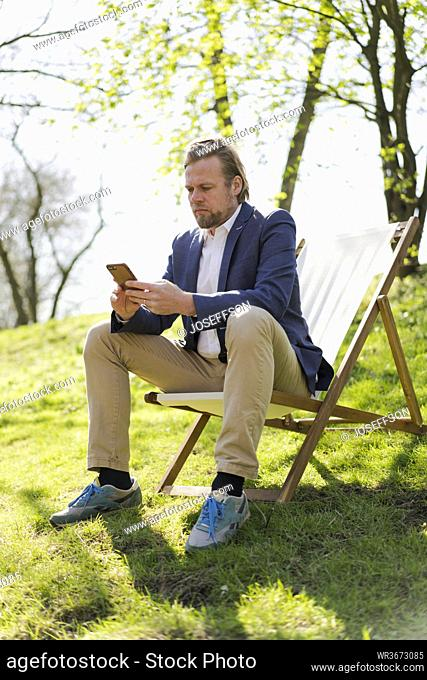 Mature businessman text messaging through mobile phone while sitting on chair at park