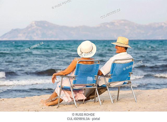 Couple on deckchairs on beach, Palma de Mallorca, Spain