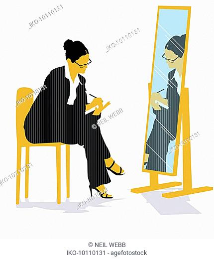 Businesswoman looking in mirror