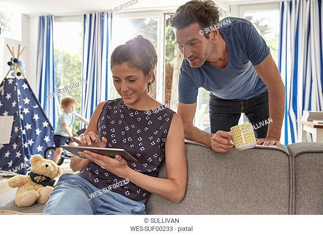 Couple using tablet at home with boy in background