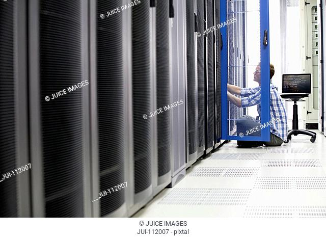 Technician with laptop checking server in data centre