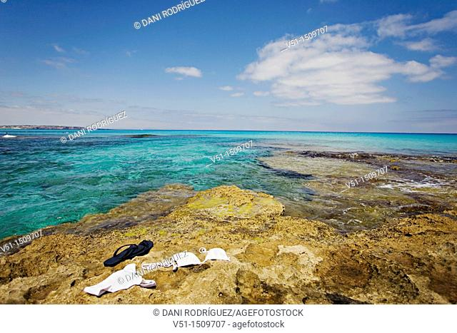 Bikini and sandals on the rocks in a beach in Formentera, Balearic Islands