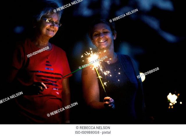 Senior and mature woman igniting sparklers together at night on independence day, USA