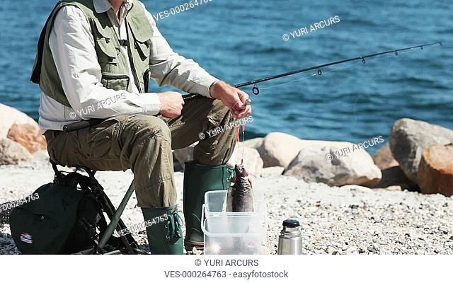 Happy senior man holding up two fish while sitting with all his fishing gear alongside some water on a sunny day