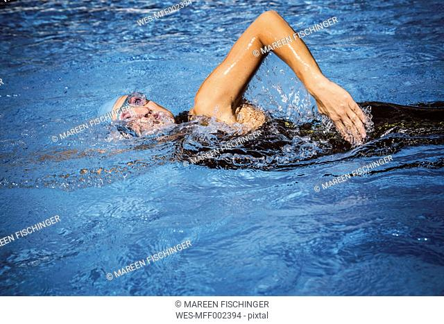 Female triathlete swimming in pool