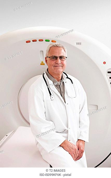 Male doctor by CT scanner