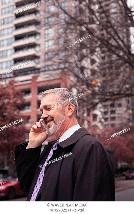 businessman using phone while standing against building