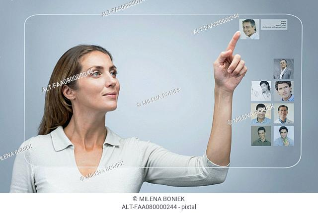 Woman using internet dating service on advanced touch screen interface