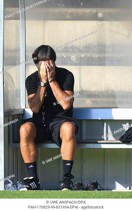 Germany's coach Joachim Loew is covering his face with his hands during a training session of the German national soccer team on the training grounds of the...