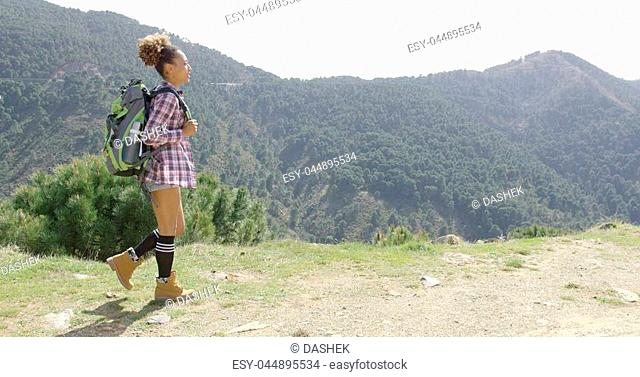 Side view of young female tourist with backpack walking on hill with beautiful mountains on background