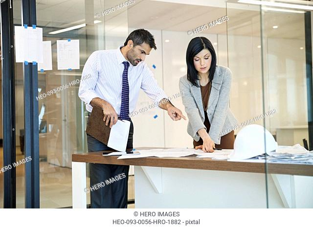 Colleagues reviewing documents in glass office