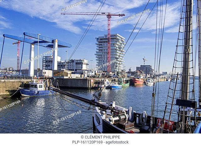 Two-master sailing vessel Nele and new flats being build for real estate project Oosteroever in the Ostend harbour along the Belgian North Sea coast, Belgium