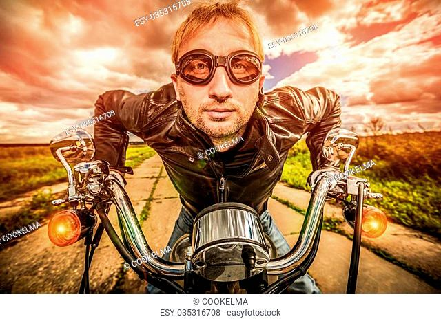 Funny Biker in sunglasses and leather jacket racing on the road (fisheye lens). Filter applied in post-production