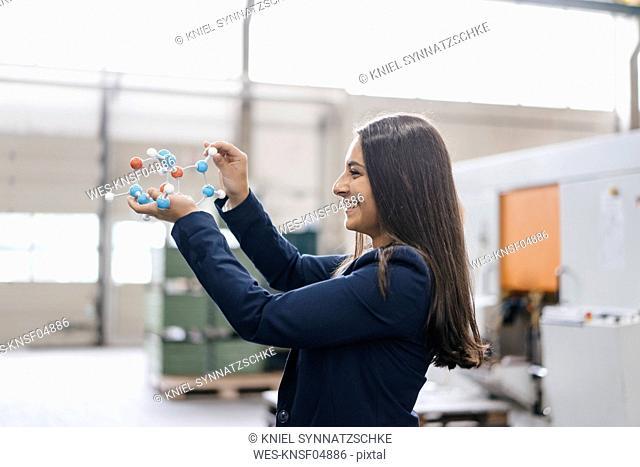 Confident woman working in high tech enterprise, holding molecule model
