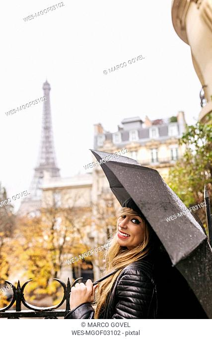 France, Paris, young woman under umbrella with the Eiffel Tower in the background