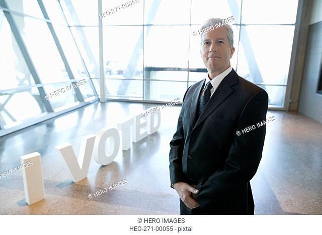 Portrait confident businessman near I Voted text