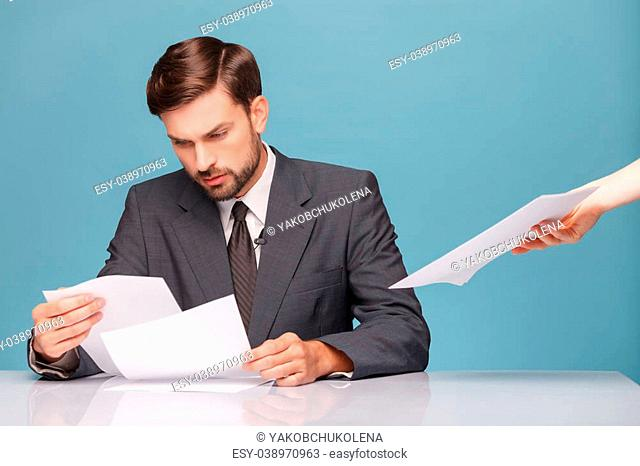 Handsome male tv newscaster is preparing for his report. He is reading documents with seriousness and sitting at desk. The female hand gives him papers