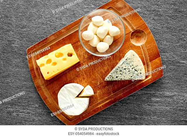 different kinds of cheese on wooden cutting board