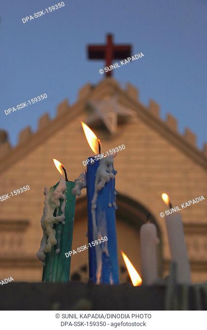 Candles melted burning against St. Patrick church ; Pune ; Maharashtra ; India