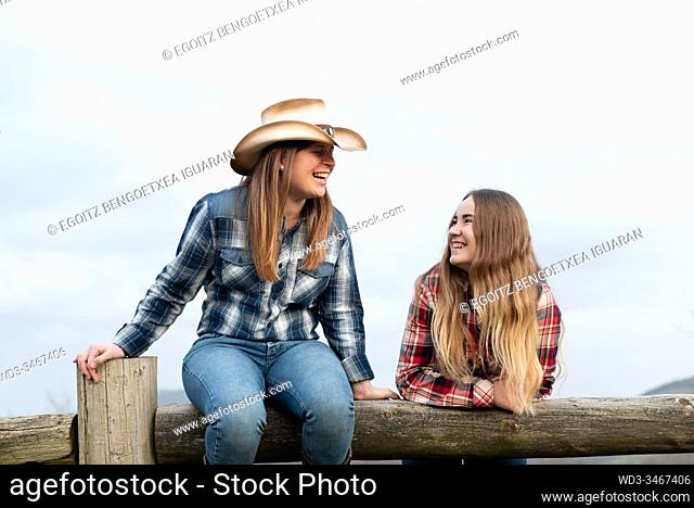 Young and teenager blonde cowgirls laughing on a wooden barrier