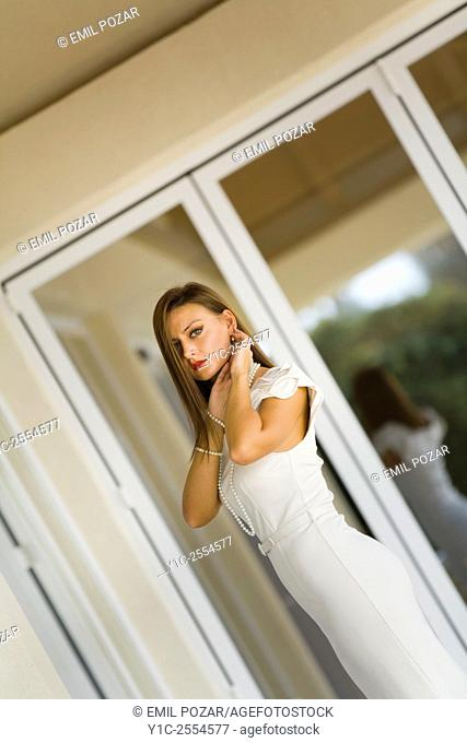Stock Photo - Young woman in White dress framed by window