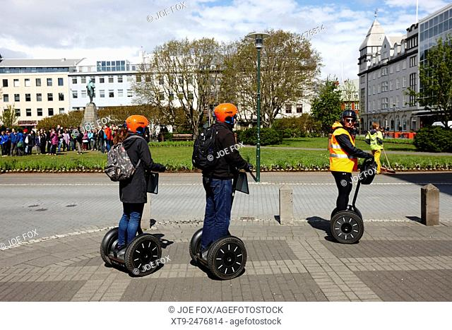 tourists on guided segway tour in austurvollur public square Reykjavik iceland