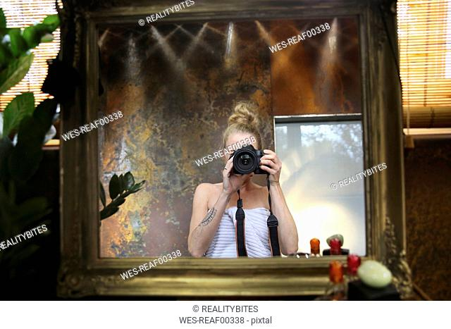 Mirror image of woman taking selfie with camera in bathroom