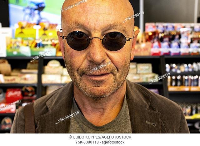 Tilburg, Netherlands. Balding man wearing sunglasses inside an E-Cigarette Shop, informing himslef about socalled nicotine replaced smoking