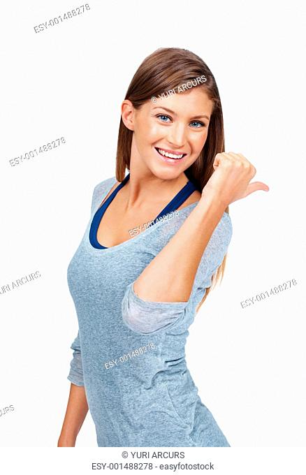 Portrait of happy young woman pointing at something over white background