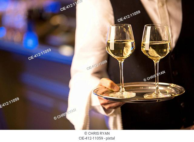 Close up bartender carrying white wine glasses on tray