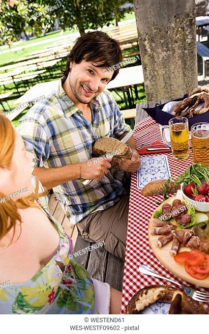 Germany, Bavaria, Upper Bavaria, People having cold snack in beer garden