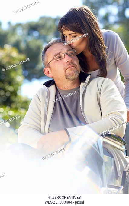 Woman kissing man in wheelchair