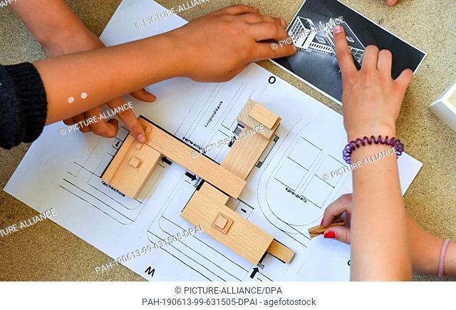 13 June 2019, Saxony-Anhalt, Dessau-Roßlau: Students of the Dessau Peace School rebuild the Bauhaus building with building blocks